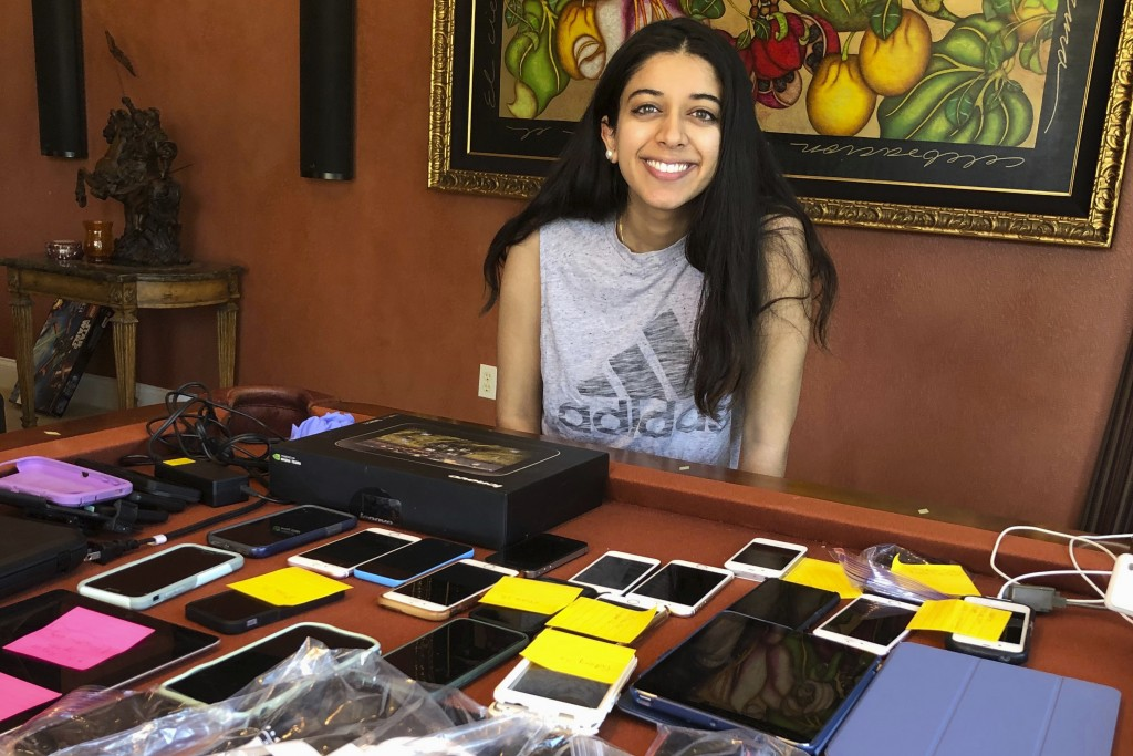 In this May 3, 2020 provided by TeleHealth Access for Seniors, Yale student Hannah Verma poses for a photograph near a table with mobile devices in Lo...