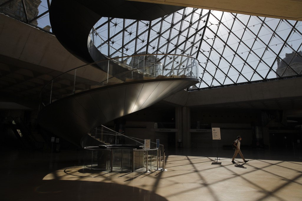 A man walks at the Louvre museum ahead of its reopening next July 6, in Paris, Tuesday, June 23, 2020. After four months of virus-imposed inactivity, ...