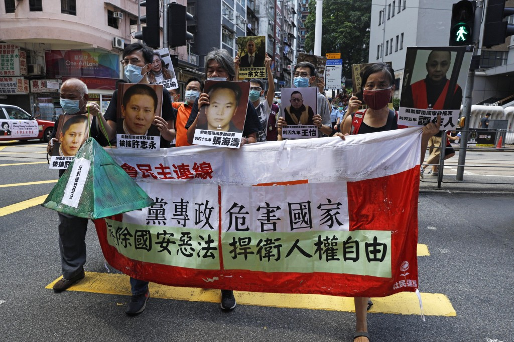 Pro-democracy demonstrators hold up a banner and portraits of jailed Chinese civil rights activists, lawyers and legal activists as they march to the ...