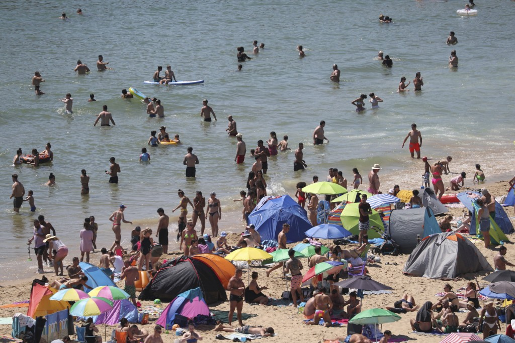 Crowds gather at the water's edge as hot weather draws crowds to the beach in Bournemouth, England, Thursday June 25, 2020. Coronavirus lockdown restr...
