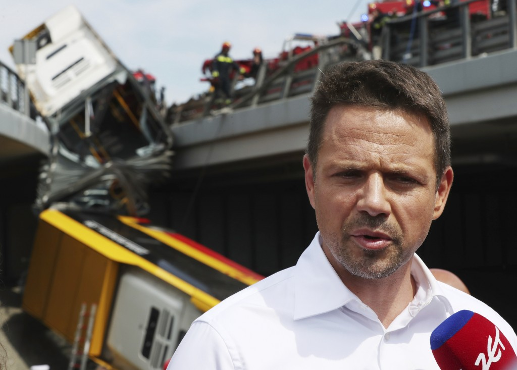 Warsaw Mayor Rafal Trzaskowski talking to reporters at the site of a city bus crash that killed one person and injured over 20 people when the articul...
