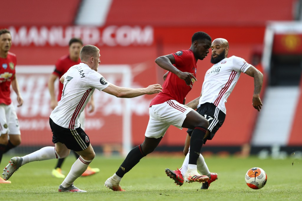 Manchester United's Paul Pogba, center, controls the ball as Sheffield United's John Lundstram, left, and David McGoldrick try to stop him during the ...