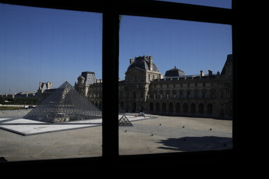 The pyramid of the Louvre museum is pictured through a window during a visit as part of its reopening next July 6, in Paris, Tuesday, June 23, 2020. B...