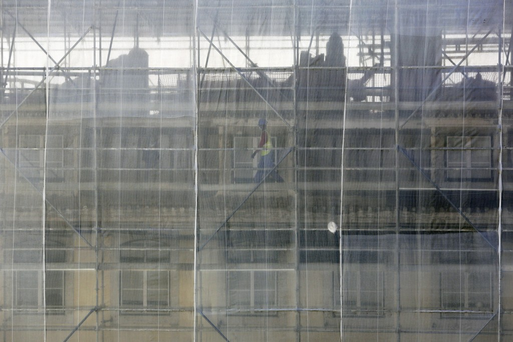 In this photo taken Wednesday, June 24, 2020, a construction worker wearing a face mask walks on scaffolding at a construction site in Lisbon. Portuga...
