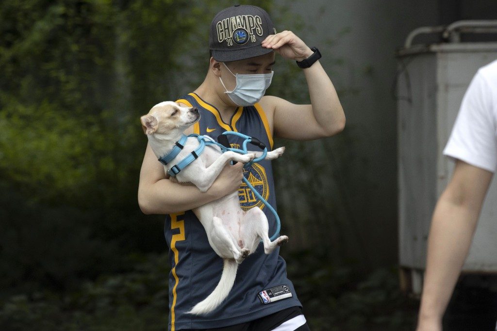 A man wearing a mask carries his dog along a street in Beijing on Thursday, June 25, 2020. In China, where the virus first appeared late last year, an...