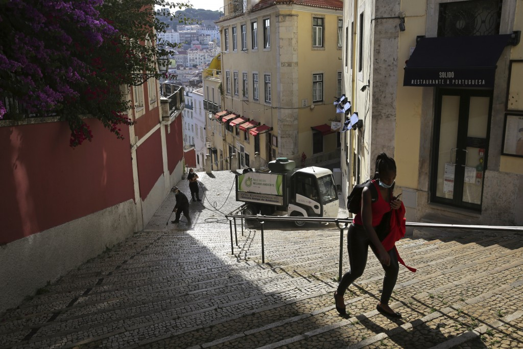 In this photo taken Wednesday, June 24, 2020, a woman wearing a face mask walks past workers washing the street in Lisbon's old center. Portugal avoid...