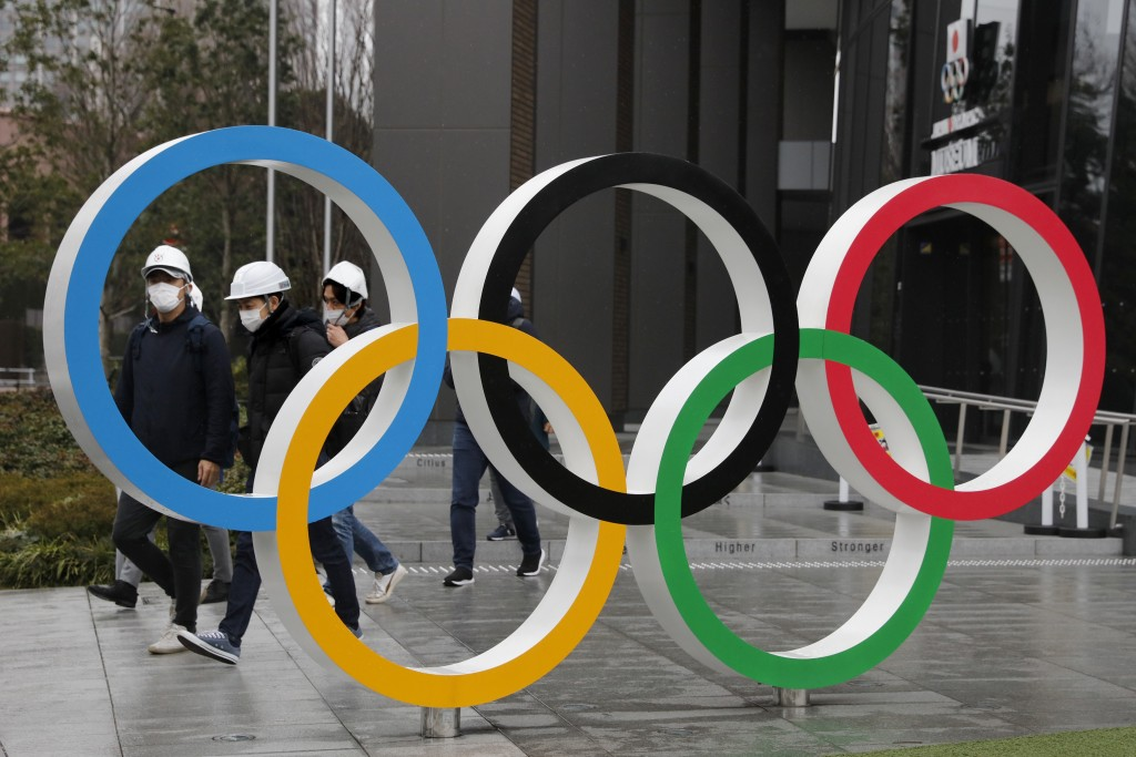 FILE - In this March 4, 2020, file photo, people wearing masks walk past the Olympic rings near the New National Stadium in Tokyo. Local Japanese spon...
