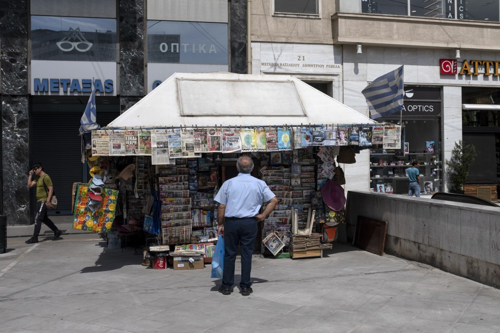 A man checks newspapers' front pages at a kiosk in Athens, on Friday, June 5, 2020. The European Commission says Greece is likely to suffer deepest re...