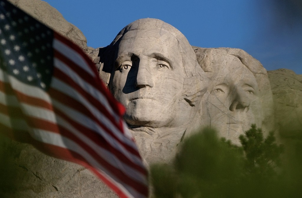 FILE - In this Sept. 11, 2002, file photo, the sun rises on Mt. Rushmore National Memorial near Keystone, S.D. as the flag is flown at half staff in h...