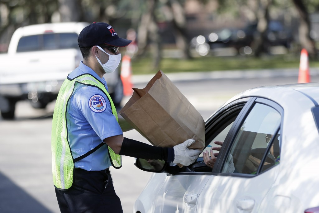A member of Orange County Fire Rescue passes out personal protective equipment (PPE) items including disposable face masks, reusable masks and hand sa...