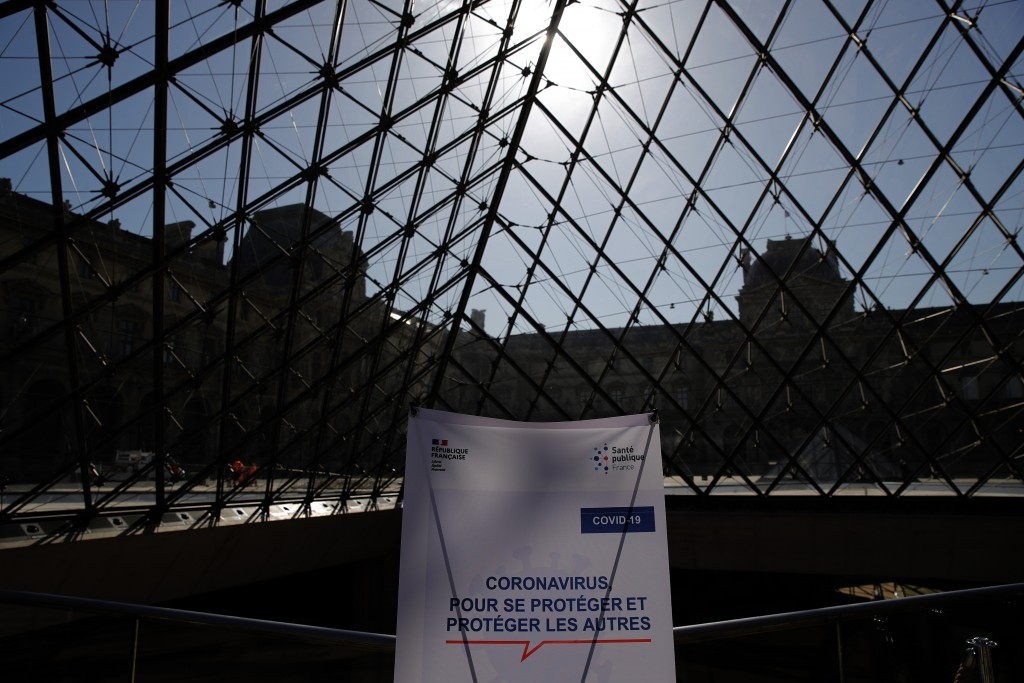 A sign shows measures to take against the coronavirus at the Louvre museum during a visit ahead of its reopening next July 6, in Paris, Tuesday, June ...