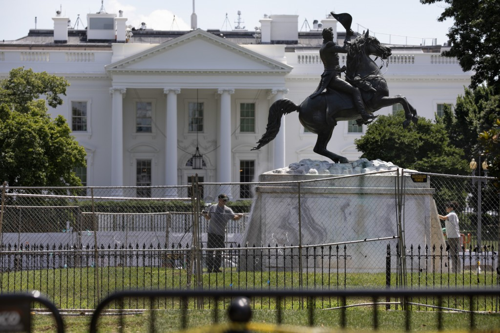The base of the statue of former president Andrew Jackson is power washed inside a newly closed Lafayette Park, Wednesday, June 24, 2020, in Washingto...