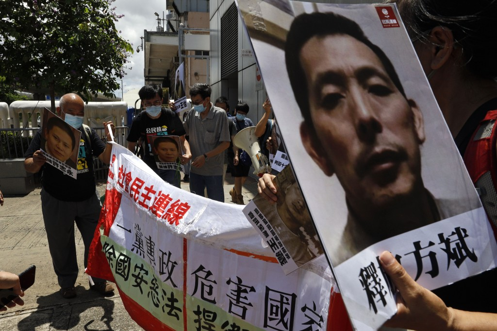 Pro-democracy demonstrators hold up portraits of jailed Chinese civil rights activists, lawyers and legal activists as they march to the Chinese liais...
