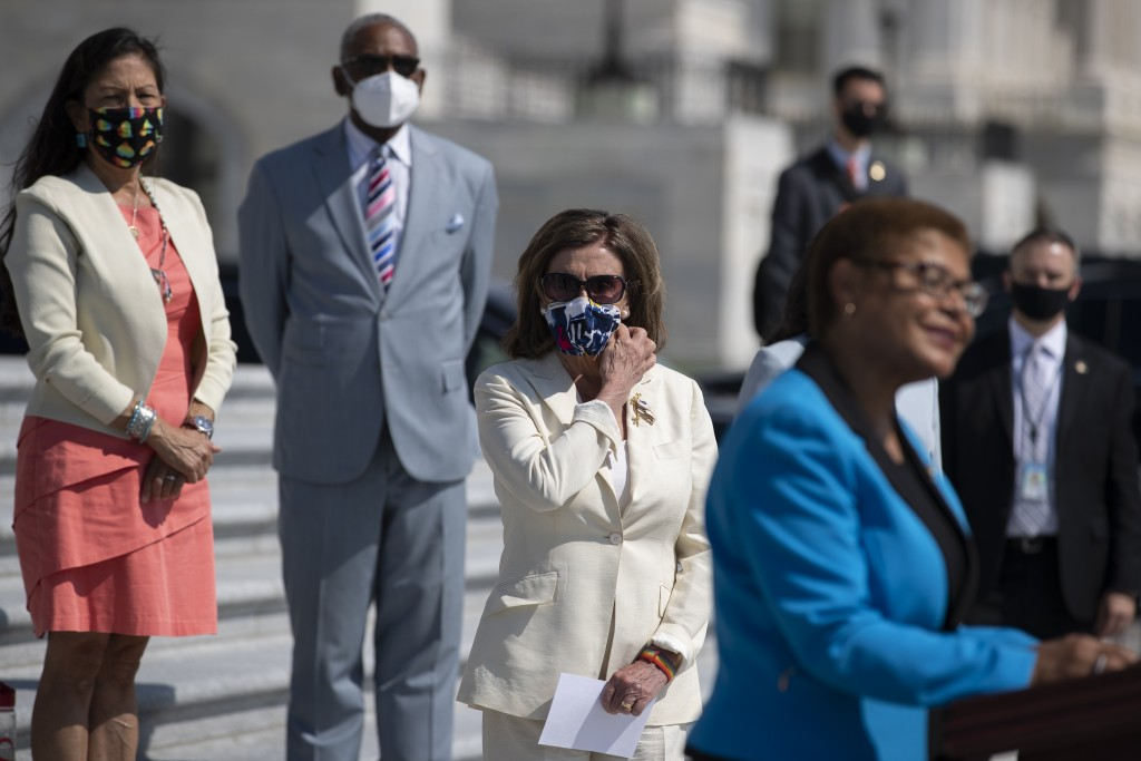 House Speaker Nancy Pelosi of Calif., adjusts her facemark as she stands with House Democrats spaced for social distancing, as Rep. Karen Bass, D-Cali...
