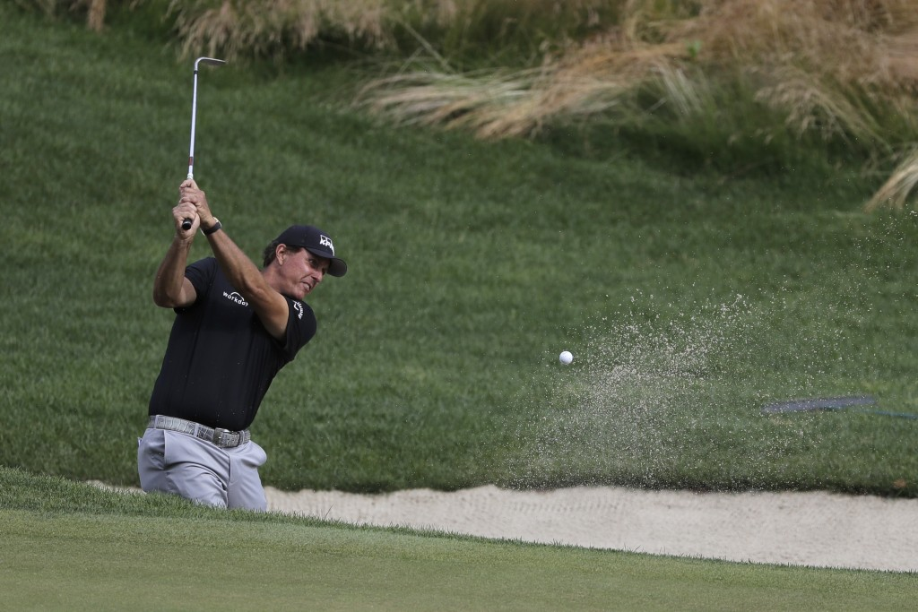 Phil Mickelson hits out of a sand trap on the 16th hole during the first round of the Travelers Championship golf tournament at TPC River Highlands, T...