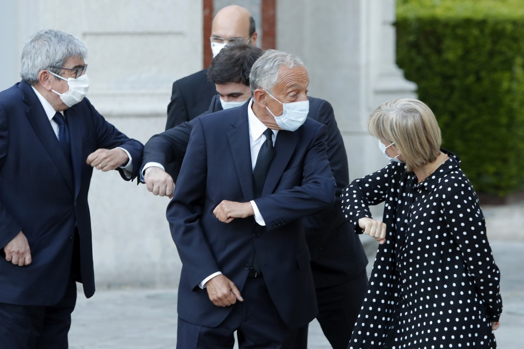 FILE - In this June 17, 2020 file photo, Portuguese President Marcelo Rebelo de Sousa bumps elbows with Health Minister Marta Temido, right, at the Be...