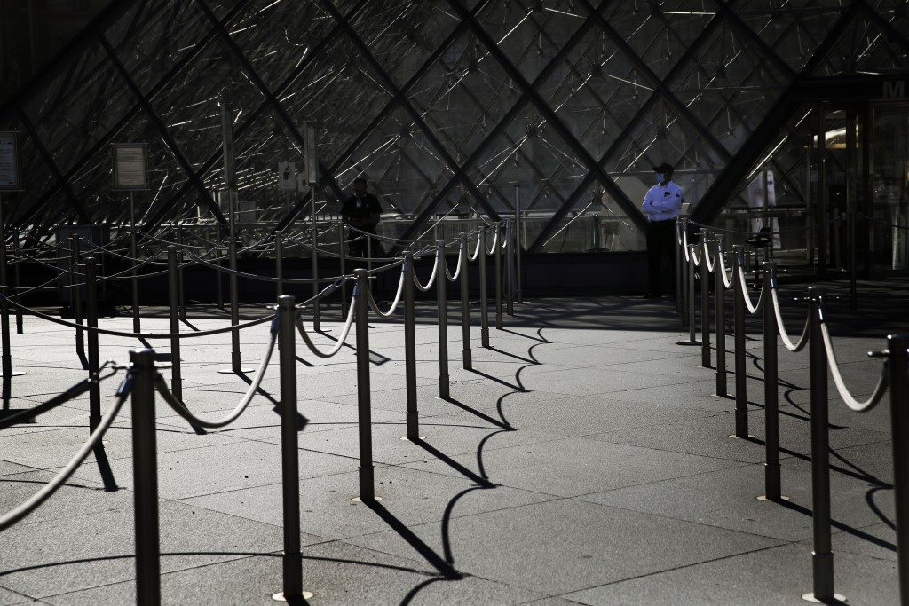 A guard stands in front of the Louvre museum entrance during a visit ahead of its reopening next July 6, in Paris, Tuesday, June 23, 2020.  Before mas...