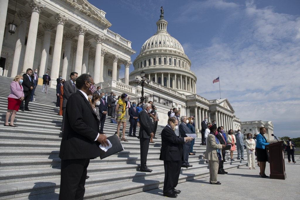 Rep. Karen Bass, D-Calif., joined by House Speaker Nancy Pelosi of Calif., and other House Democrats spaced for social distancing, speaks during a new...
