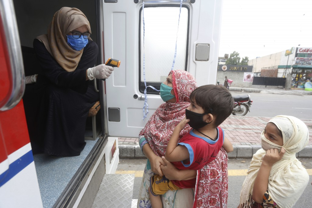 A health worker checks the body temperature of a woman at a mobile screening unit set up to control the spread of the coronavirus, in Lahore, Pakistan...