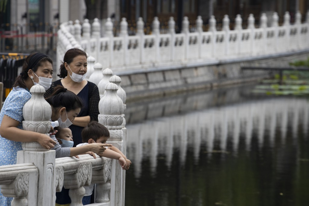 Visitors wear masks as they visit a lake-side district closed off due to the recent outbreak of coronavirus in Beijing Thursday, June 25, 2020. In Chi...