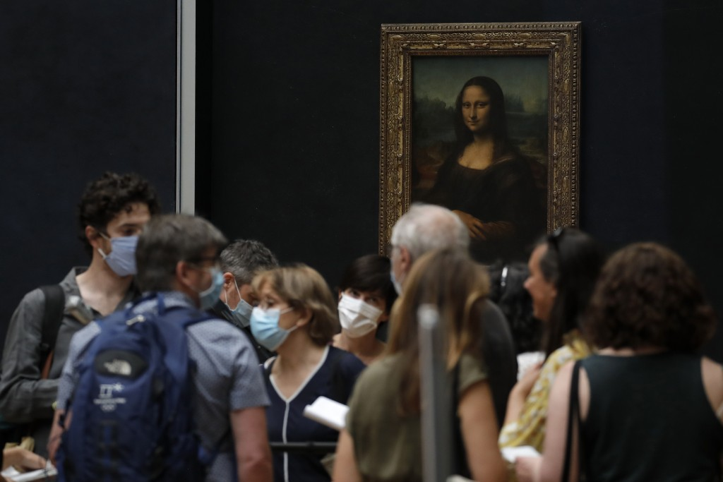 Journalists stand in front of Leonardo da Vinci's Mona Lisa during a visit of the Louvre museum ahead of its reopening next July 6, in Paris, Tuesday,...
