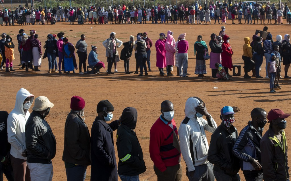 FILE — In this May 20, 2020 file photo, people affected by the coronavirus economic downturn line up to receive food parcels in Pretoria, South Africa...
