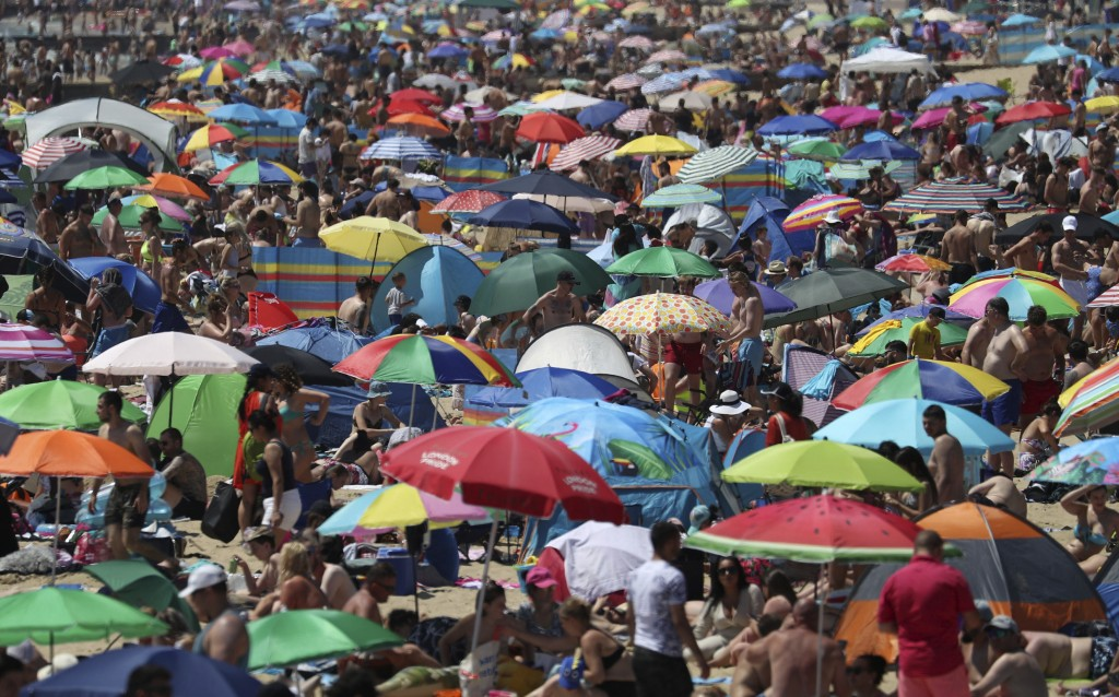 Crowds gather on the beach in Bournemouth, England, Thursday June 25, 2020, as coronavirus lockdown restrictions have been relaxed. According to weath...