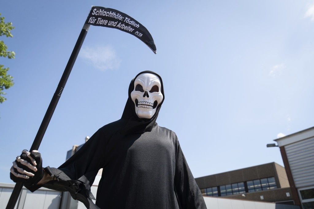 An activist of the animal protection organization Peta disguised as death stands in front of a delivery entrance of the meat and sausage manufacturer ...