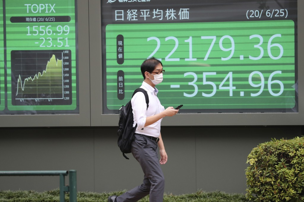 A man walks by an electronic stock board of a securities firm in Tokyo, Thursday, June 25, 2020. Shares declined in Asia on Thursday after a sharp ret...