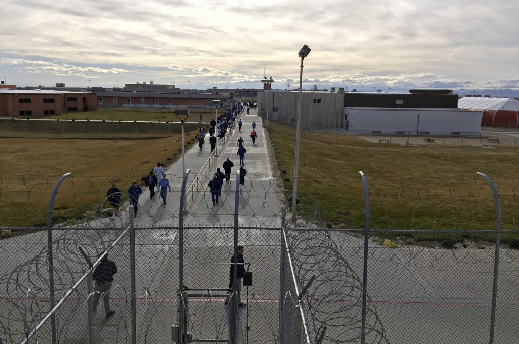 FILE - In this Jan. 30, 2018, file photo, inmates walk across the grounds of the Idaho State Correctional Institution in Kuna, Idaho. Hundreds of thou...