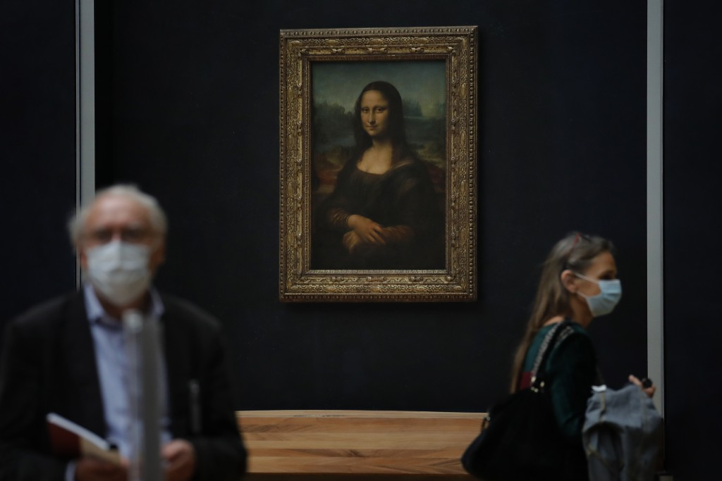 Journalists walk past Leonardo da Vinci's Mona Lisa during a visit of the Louvre museum ahead of its reopening next July 6, in Paris, Tuesday, June 23...