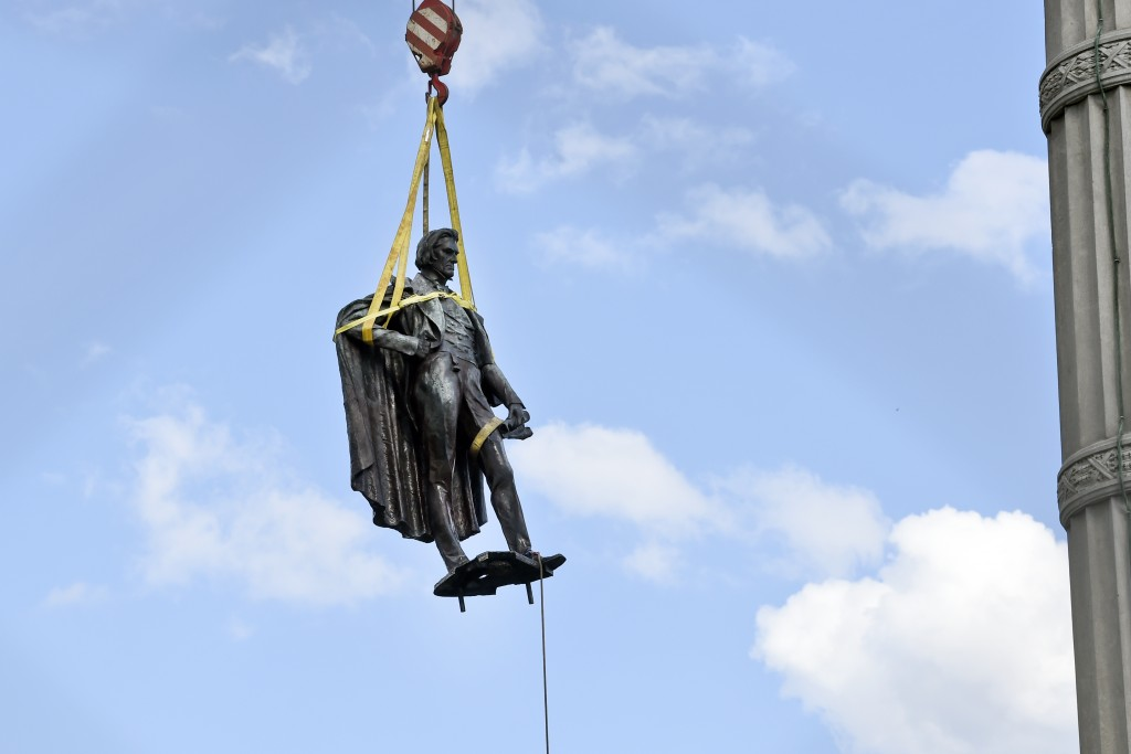 A statue of former U.S. vice president and slavery advocate John C. Calhoun is raised by crews after its removal from a 100-foot-tall monument on Wedn...