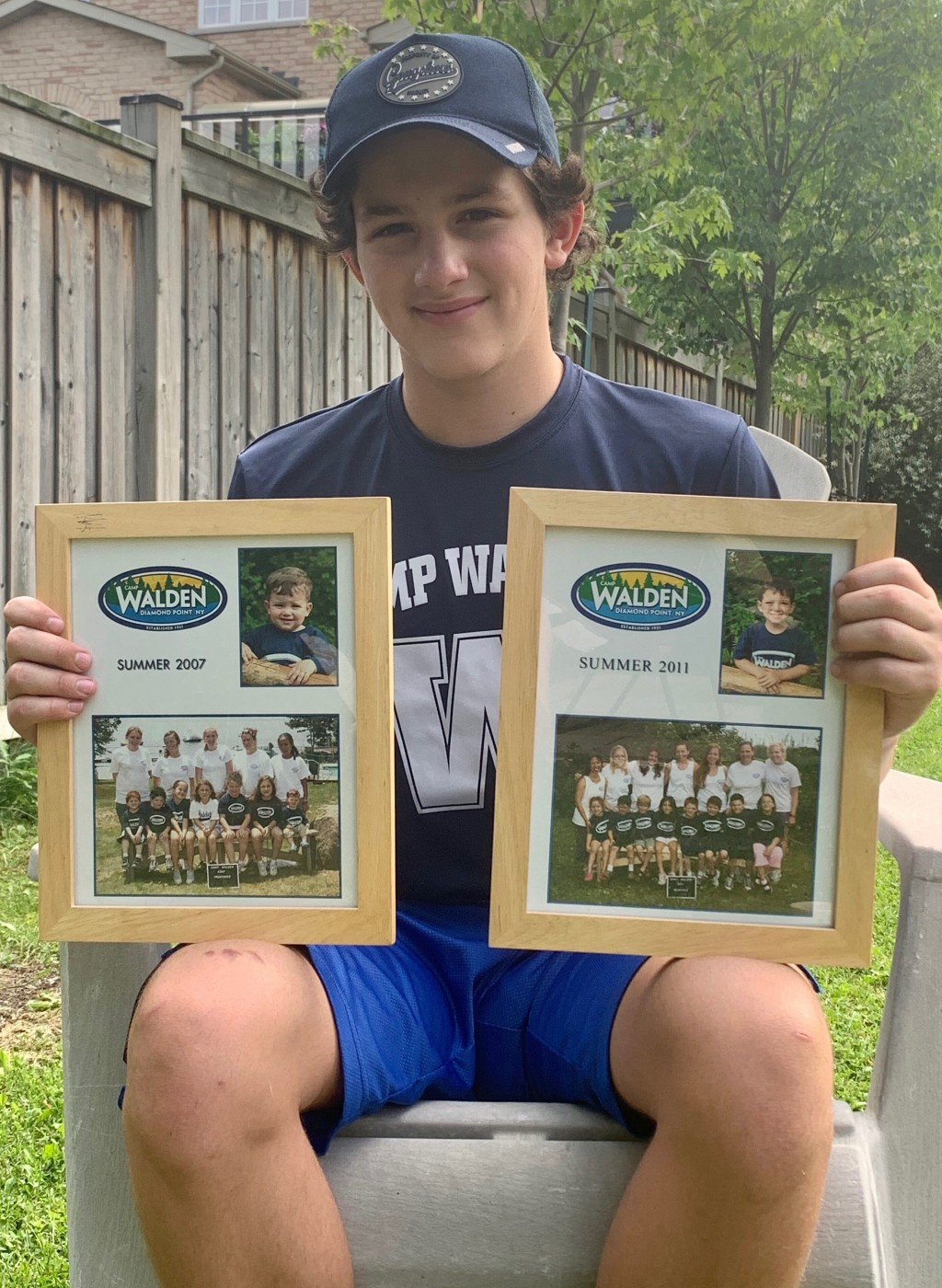 In this June 22, 2020, photo provided by Ashley Sederoff, 14-year-old Rory Sederoff holds framed photos of his previous summers at Camp Walden in 2007...
