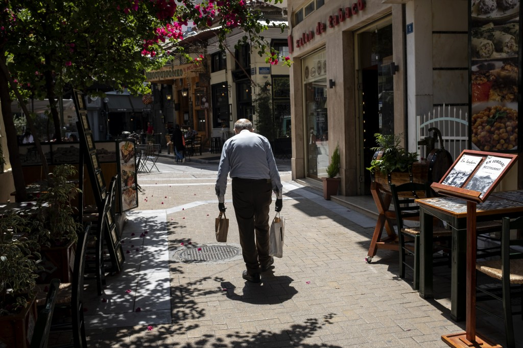 A man carries shopping bags on a pedestrian street, in Athens, on Friday, June 5, 2020. The European Commission says Greece is likely to suffer deepes...