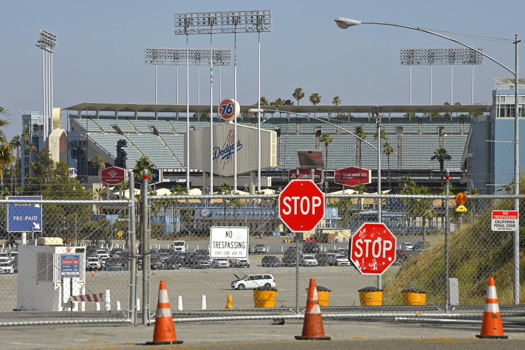 Dodger Stadium stands behind locked gates Wednesday, June 24, 2020, in Los Angeles. By the time Major League Baseball returns in late July, it will ha...