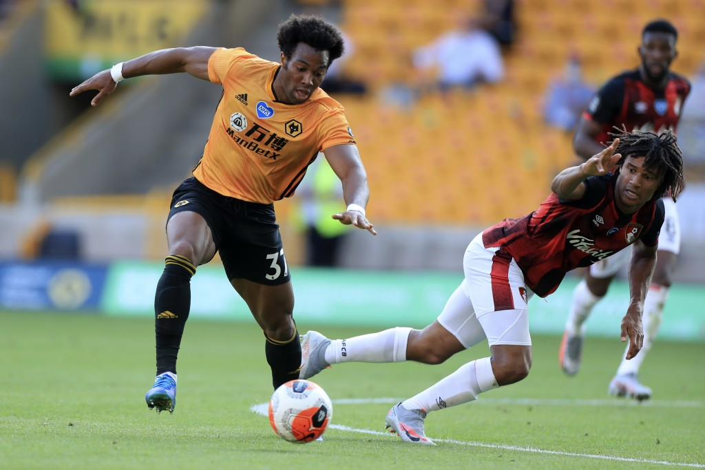 Wolverhampton Wanderers' Adama Traore, left, controls the ball next to Bournemouth's Nathan Ake during the English Premier League soccer match between...