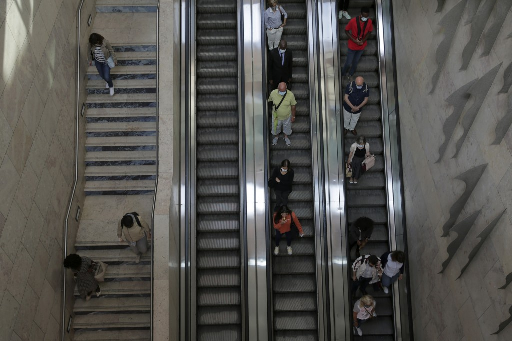 In this photo taken Wednesday, June 24, 2020, commuters leave Lisbon's Rossio train station. Portugal avoided the dramatic numbers of infections and d...