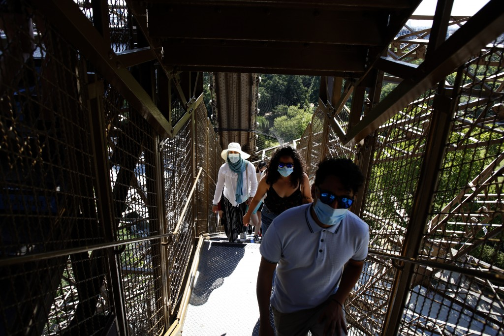 People climb stairs as they visit the Eiffel Tower, in Paris, Thursday, June 25, 2020. The Eiffel Tower reopens after the coronavirus pandemic led to ...