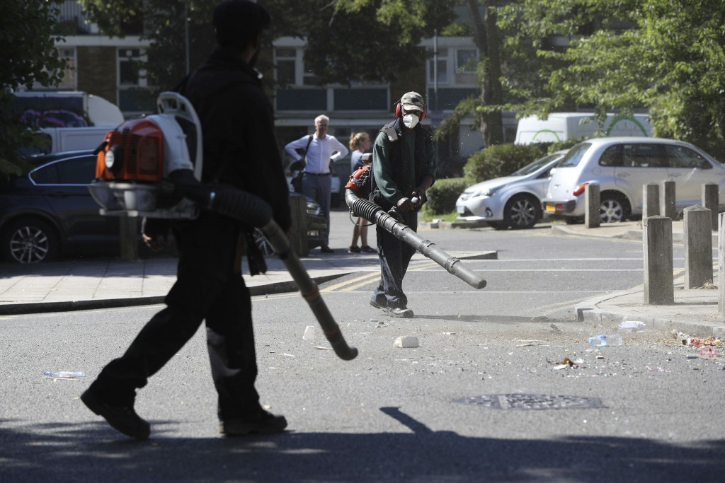 Volunteers clean up the streets following overnight violent confrontations with police, in the Brixton area of London, Thursday June 25, 2020.  Author...