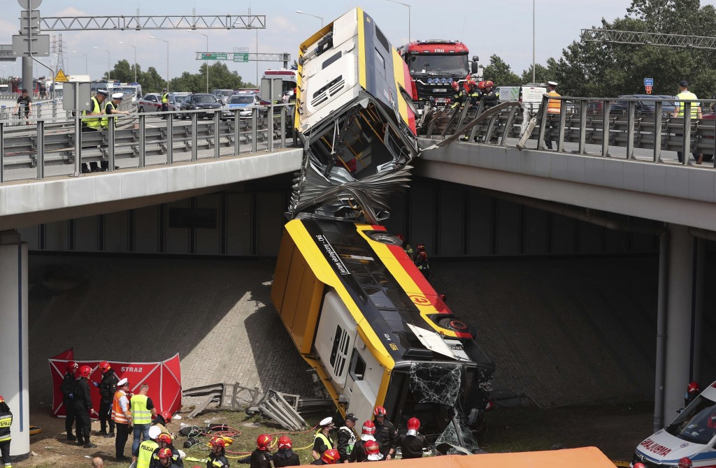 The wreckage of an articulated city bus hangs off an overpass after a fatal accident in Warsaw, Poland, on June 25, 2020. The accident forced Warsaw M...