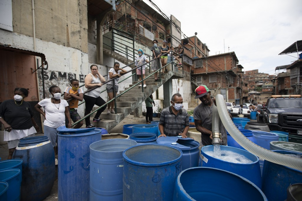 A residents fills a container with water provided by a government tanker truck in the Petare neighborhood of Caracas, Venezuela, Monday, June 15, 2020...