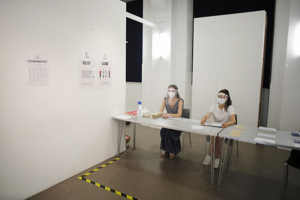 People wearing face mask and visor to protect against coronavirus sit behind a glass shield during a rehearsal of the vote for the local elections sch...