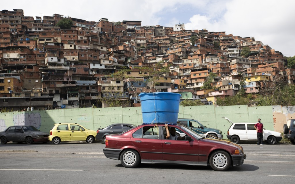 A car drives past hauling a plastic water tank on it's rooftop, in the Petare neighborhood of Caracas, Venezuela, Friday, June 5, 2020. An estimated 8...