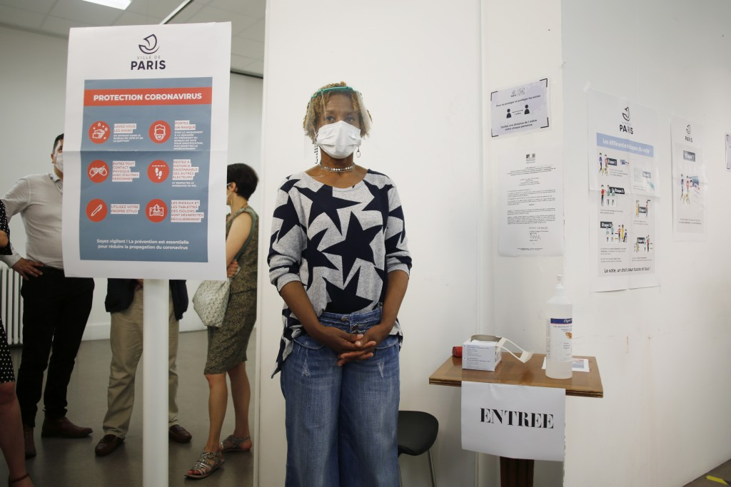 A woman wearing a face mask and visor to protect against coronavirus stands at the entrance of a polling station during a rehearsal of the vote for th...