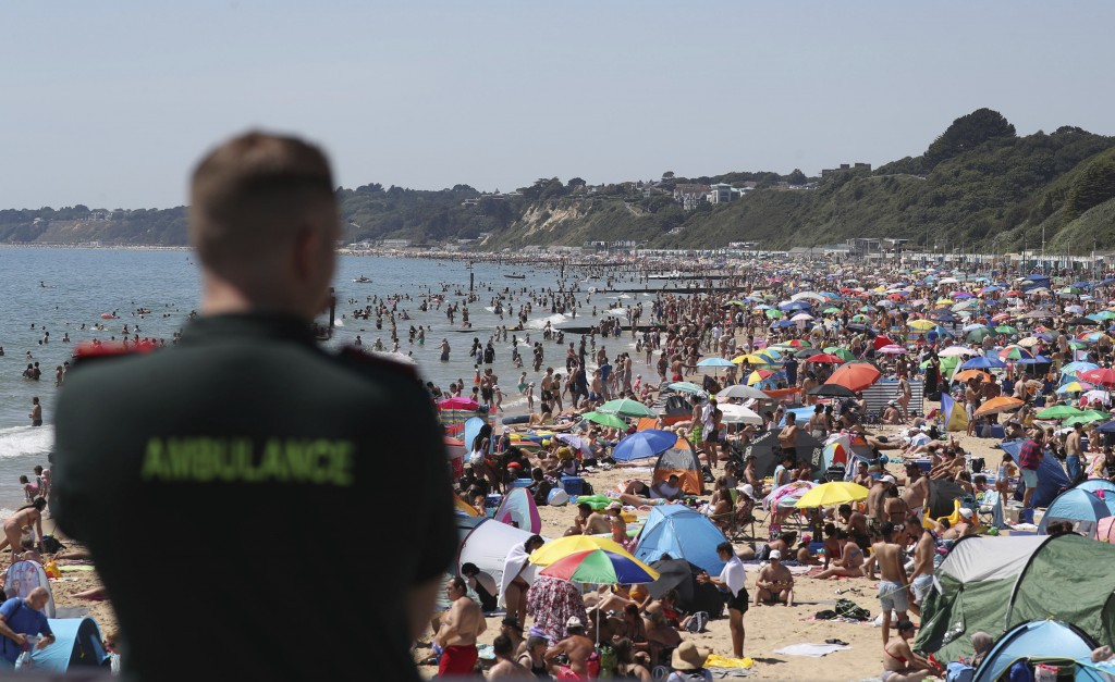 A member of the Ambulance service looks out at people crowded on the beach in Bournemouth, England, Thursday June 25, 2020, as coronavirus lockdown re...