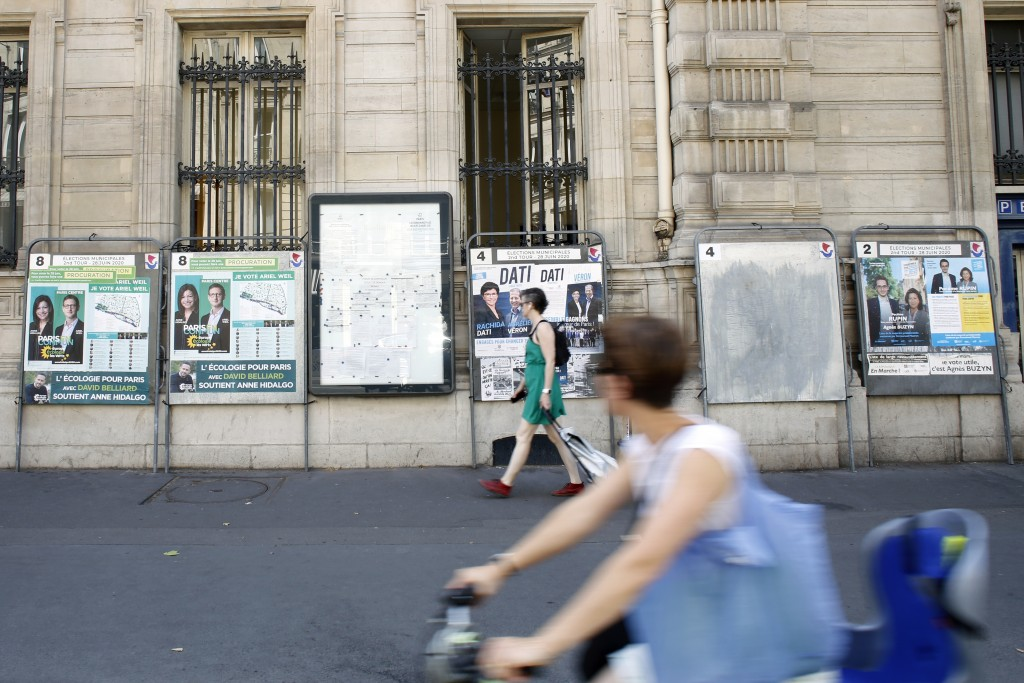 People walk past campaign posters for the upcoming local elections in Paris, Friday, June 26, 2020. France is to hold its Covid-19 delayed second roun...