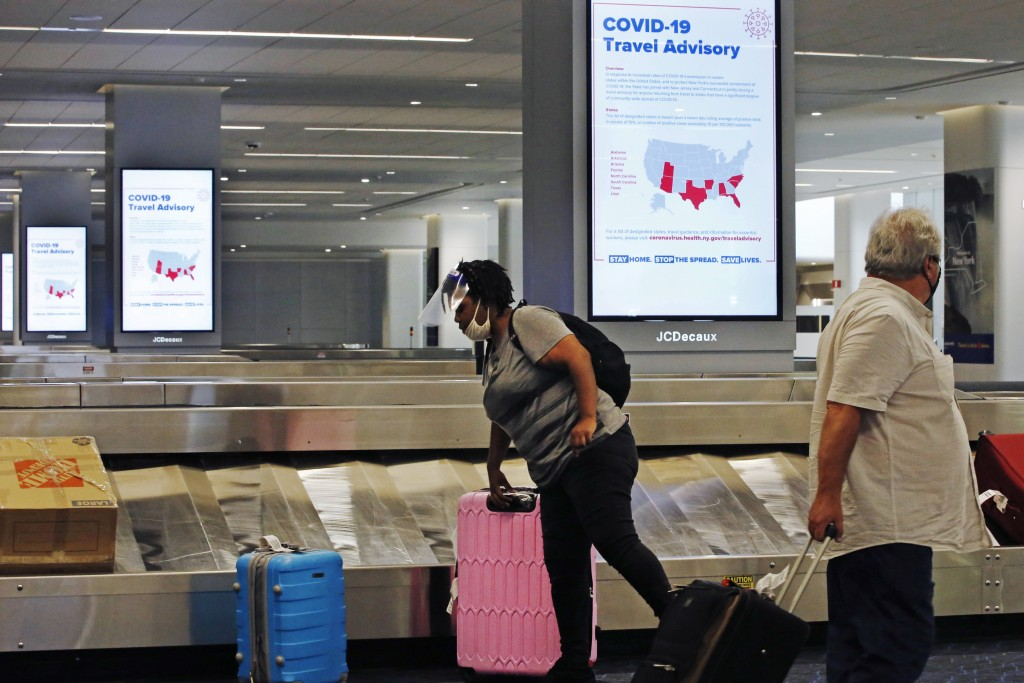 An arriving passenger wearing a face shield, left, collects her luggage in the baggage claim area of LaGuardia Airport's Terminal B, Thursday, June 25...