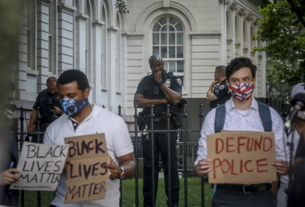 A New York City police officer, among a detail of police guarding City Hall, watches as organizers with City Workers4Justice–an activist organization ...