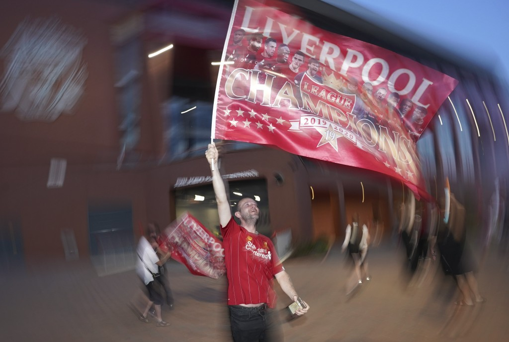 A Liverpool supporter celebrates outside Anfield Stadium in Liverpool, England, Thursday, June 25, 2020 after hearing Chelsea had scored in the Englis...