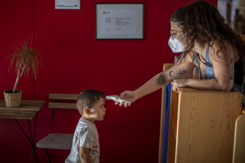 Hugo, 3, has his temperature taken by a teacher as he arrives at Cobi kindergarten in Barcelona, Spain, Friday, June 26, 2020. Spain's cabinet will ex...